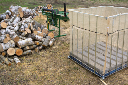 storage bin: Heap of firewood with storage bin and tractor�s splitting attachment. Stock Photo