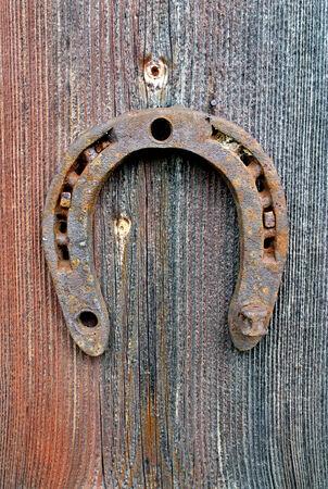 A rusty horseshoe fixed on old farm wall.