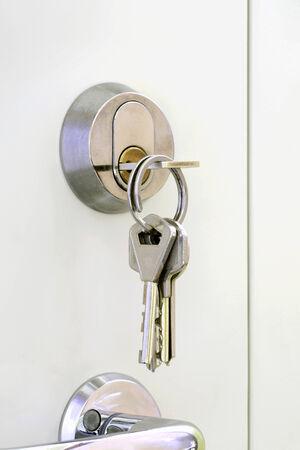 Bunch of keys hanging at the door lock  photo