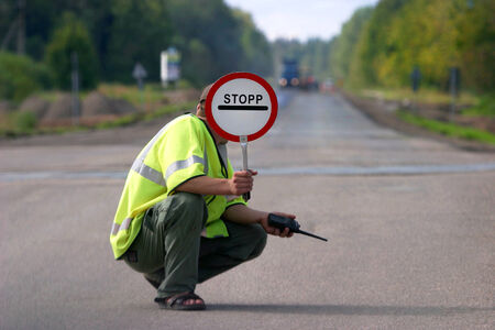 Road maintenance works - road worker with traffic sign   photo