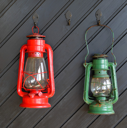 Two vintage storm lanterns hanging on wooden wall  in Aland Islands   photo