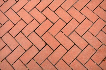 Red fishbone pavement parquet background.
