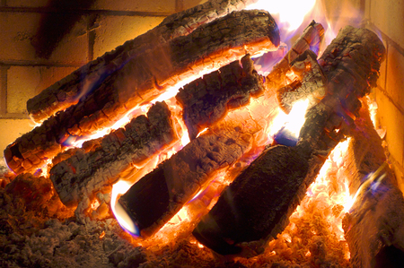 Burning logs and glowing ashes in fireplace.