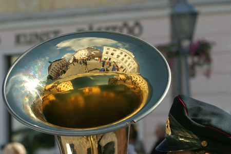 brass instrument: Bandsman with brass instrument reflecting town hall square in Tartu, Estonia.