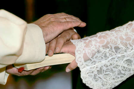 clerical: Church wedding: clerical marriage oath with hands on bible book. Stock Photo