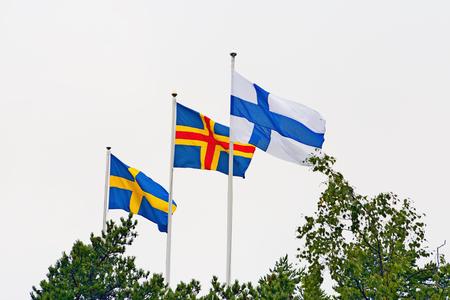 autonomia: Banderas de Suecia, Islas Aland y Finlandia contra el cielo en verano.