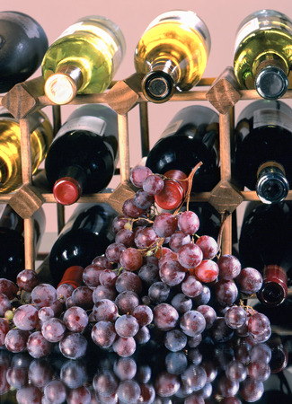 stockpile: Wine bottles stored in wooden holder, red grapes in foreground. Stock Photo