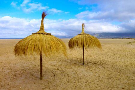tarifa: Tarifa sand beach in Spain with two sunshade umbrellas. Stock Photo