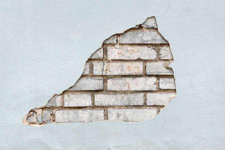 Poor plastering work has revealed white bricks.
