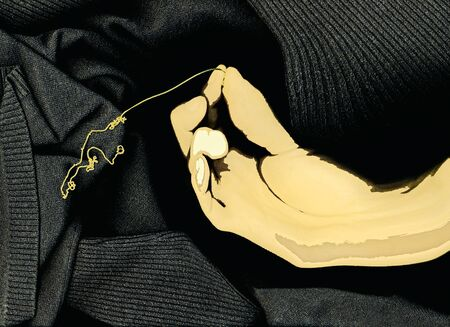 coquetry: Hand holding gold necklace against black sweater (digitally altered). Stock Photo