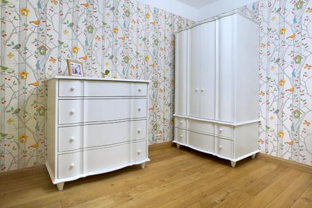 bedroom furniture: A corner of children bedroom with white furniture.