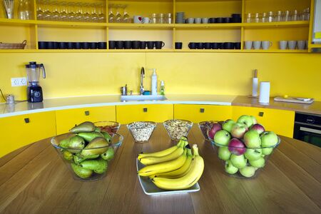 roomy: Fruits and snacks on table in roomy stylish kitchen. Stock Photo
