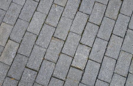 Grey pavement made of small granite tiles, background. Imagens