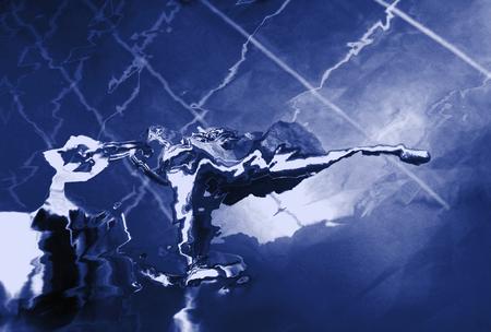 Dark blue abstract substance spreading over imaginary tiled floor.