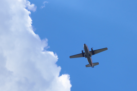 2 propeller NATO military aircraft flying in blue sky.