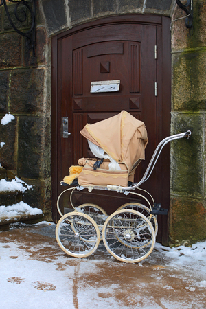 Light pink fancy baby carriage in front of entrance.