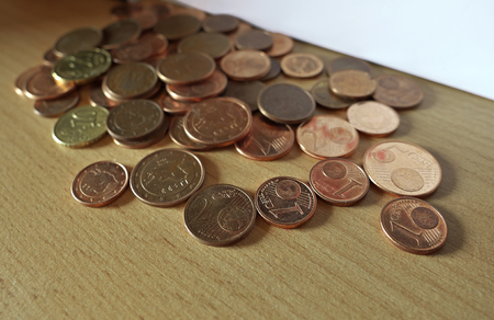 Euro coins of small value left on bookshelf (focus in foreground). Archivio Fotografico - 103738410
