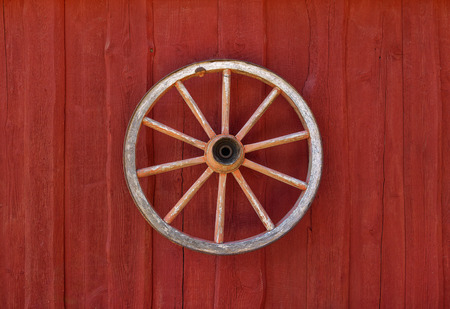 Old clean cartwheel hanging on red wooden wall as rural decoration. Imagens