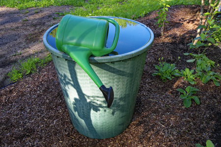 Watering barrel with watering can in garden.