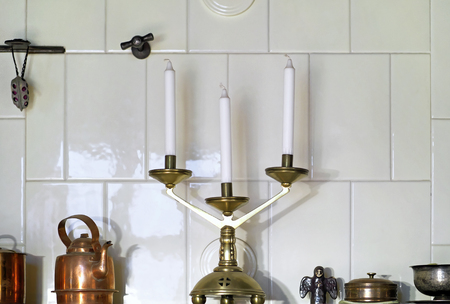 Old candelabrum and other vintage objects standing on the ledge of room heating stove covered with glazed tiles. Archivio Fotografico - 120518941