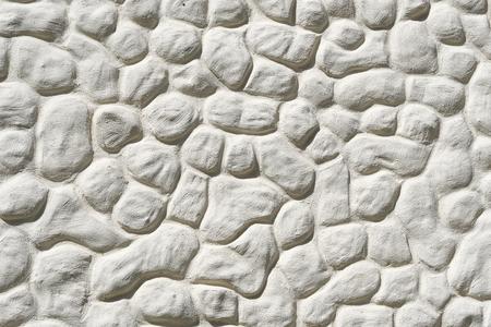 Stuccoed white fieldstone wall background. Imagens