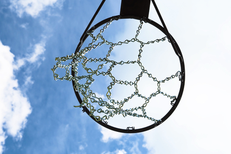 Outdoor basketball hoop with durable chain net against summer sky.