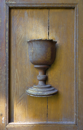 Wooden relief of grace bread cup on ancient church door.