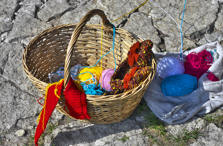 Hand crafted wicker basket with balls of yarn and some knitwork lying on robust limestone pavement. Stockfoto