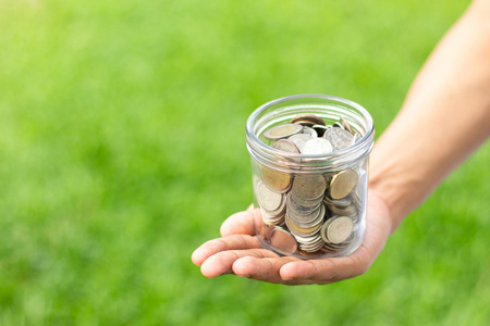 Hands holding glass jar with coins on green grass background. concept savings money  cash . copy space for text