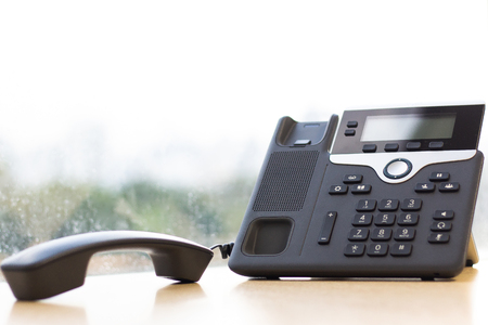 Black IP Phone on wooden table , Telephone on desk with big window city view.Modern office concept.