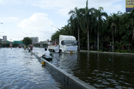 bangkok - october 28: unidentified people sit and stand in big truck to escape rising flood waters at pra pin klow bridge thonburi, in bangkok, thailand on oct. 28, 2011.
