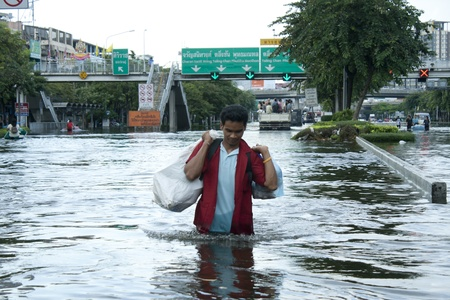 bangkok, thailand - october 28: an unidentified man walks through flood waters on pra pin klow bridge in bangkok, thailand on oct. 28, 2011. the area is on the west side of the chaopraya river.