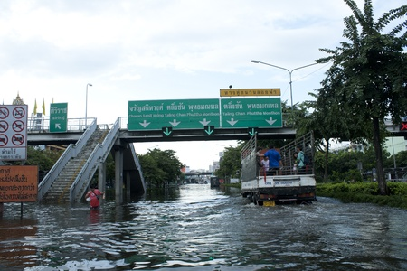 thailand flood: bangkok - october 28: unidentified people sit and stand in big truck to escape rising flood waters at pra pin klow bridge thonburi, in bangkok, thailand on oct. 28, 2011. Editorial