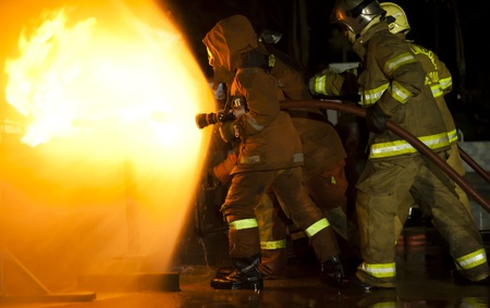 Firefighters attack a propane fire during a training exercise  photo