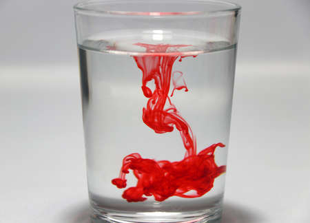 Red color drop on the water in the glass with white background, Concept of the disease is hemophilia. Foto de archivo
