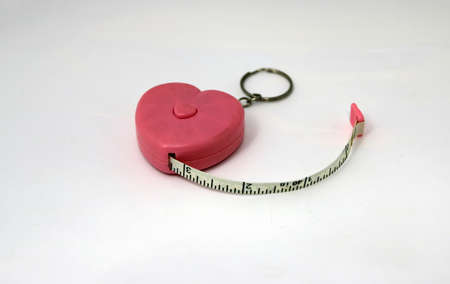 Key chain pink plastic heart measure tape on white background, show inch.