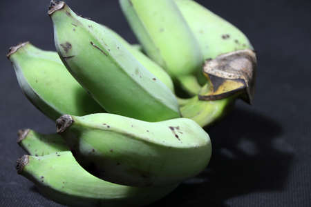 Raw and green cultivated banana put on the black floor. it is a long curved fruit that grows in clusters and has soft pulpy flesh and yellow skin when ripe.