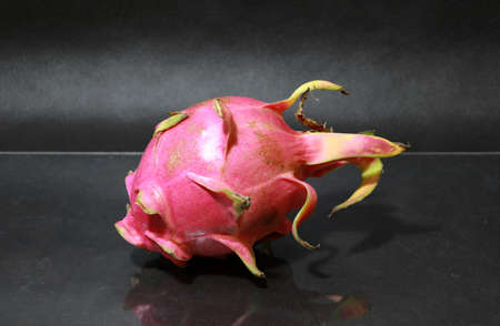 Dragon fruit on the black floor. The shape is spherical. Available in red or purple. Green cloves are attached around the fruit. Stock Photo