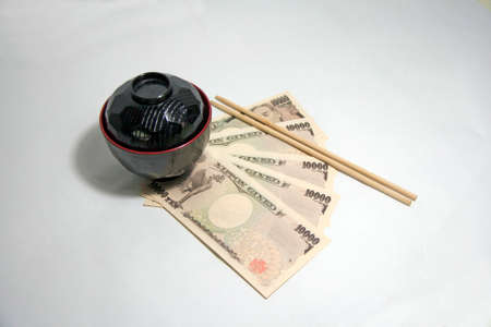 Black color red edge Miso soup bowl and wooden Chopsticks with Yen banknotes of Japan on the white background. The concept of Eat well live happily by Japanese style. Фото со стока