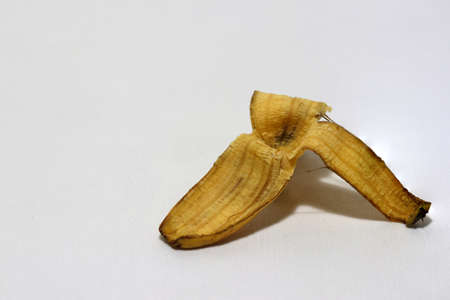 Banana peel was left on the white floor. The danger may slip. If anyone walks on it.