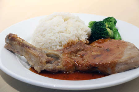 Pork Chop Steak white rice and green broccoli in the dish on the wooden table. Steak is high quality meat taken from the hindquarters of the animal, typically cut into thick slices that are cooked by broiling or frying. Stock Photo