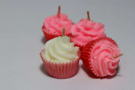 White and three pink candles in cupcake shape put on light grey background. it is a wax with a central wick that is lit to produce light as it burns.