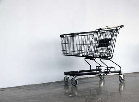 Black shopping Cart on the floor and white background. trolley is a cart supplied by a shop, especially supermarkets, for use by customers inside the shop for transport of merchandise to the checkout