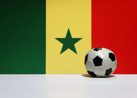 Small football on the white floor and Senegalese nation flag background in green, yellow and red color. The concept of sport.