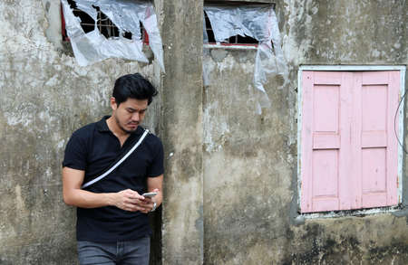 Asian man in black shirt and mobile phone in hand standing on old wall with pink window background. 스톡 콘텐츠