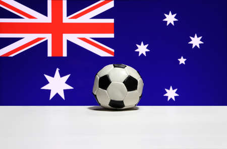 Small football on the white floor and a blue field with the Union Jack in the canton (upper hoist quarter), and six white of seven-pointed star on the blue of Australia nation flag background. The concept of sport.