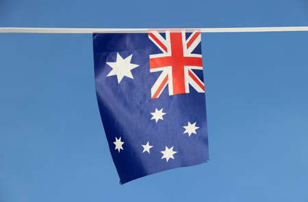 Mini fabric rail flag of Australia in blue red and white color with white star and Union Jack hanging on the rope cloth, on blue sky background.
