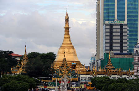 Yangon, Myanmar June 6, 2018: Golden octagon of Sula pagoda located in the heart of downtown Yangon, making it more than 2,600 years old, with building on the junction of Sule Pagoda road. 에디토리얼