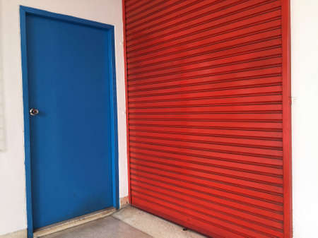 Two doors next to each other, Small blue wooden door for people to use,  big red metal door for Moving large stuff. 版權商用圖片