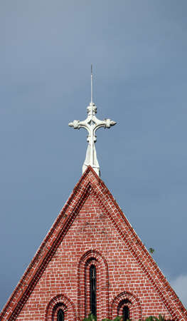 Cross on top of gable of church roof on blue sky background at cathedral of the holy trinity, the church of the province of Myanmar. Stock Photo
